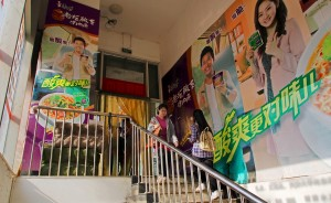 students trudge by noodle ads